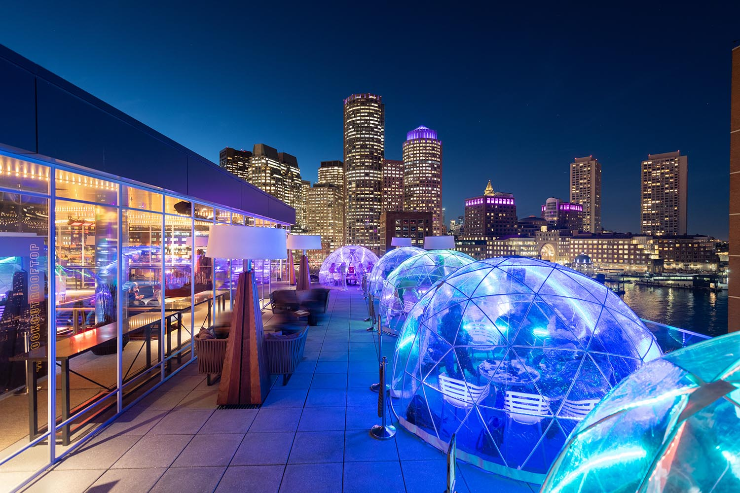 heated igloos glowing with blue light against the Boston skyilne